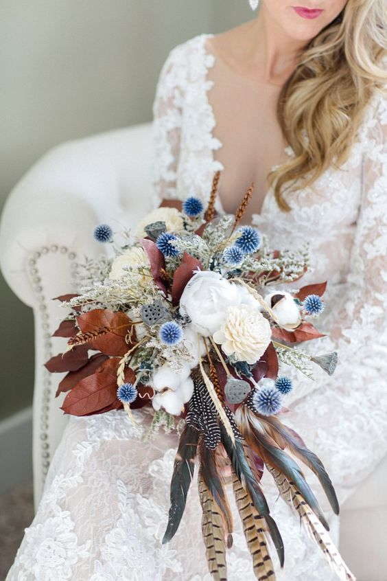 a chic fall wedding bouquet in white, blue, with dried leaves and feathers for a boho bride