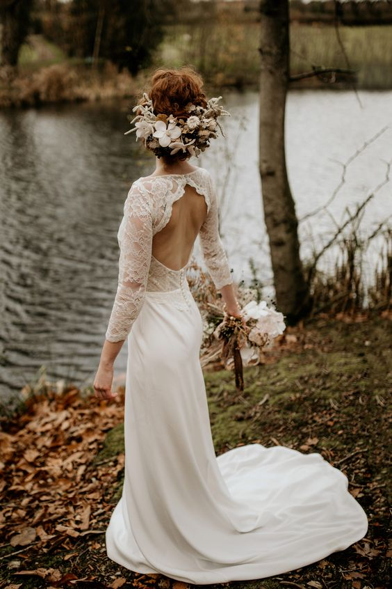 a chic mermaid wedding dress with a lace bodice, long sleeves, an open back and a plain skirt with a train