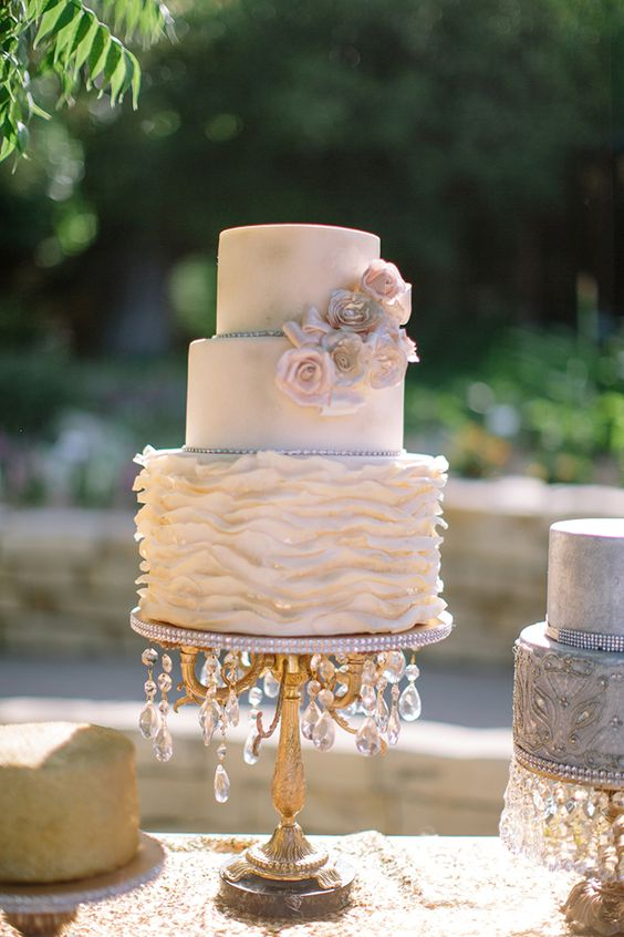 a chic neutral wedding cake with a textural tier and blush sugar blooms on a refined and chic stand