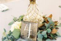 a chic wedding centerpiece of foliage, white blooms, a wooden plaque and a pineapple-shaped lantern with lights inside is awesome