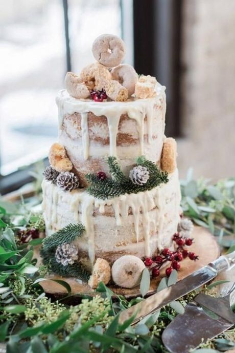 a chic winter woodland wedding cake, a naked one with creamy drip, donuts, pinecones and evergreens plus berries