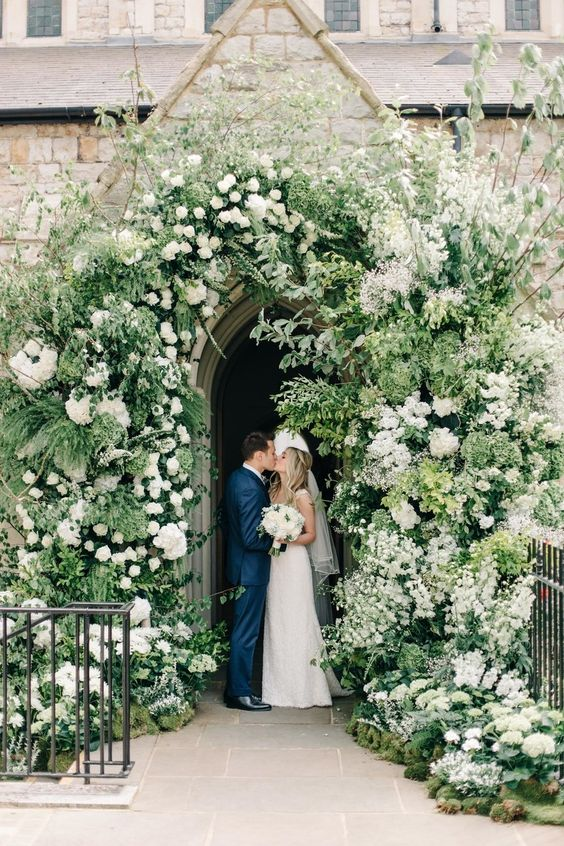 a church entrance decorated with greenery and white blooms looks chic and lush