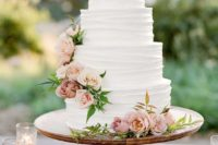 a classic textural white wedding cake with pink and blush blooms and foliage is a chic idea