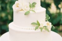 a classic white wedding cake with bead decor, foliage and white blooms is a very chic idea