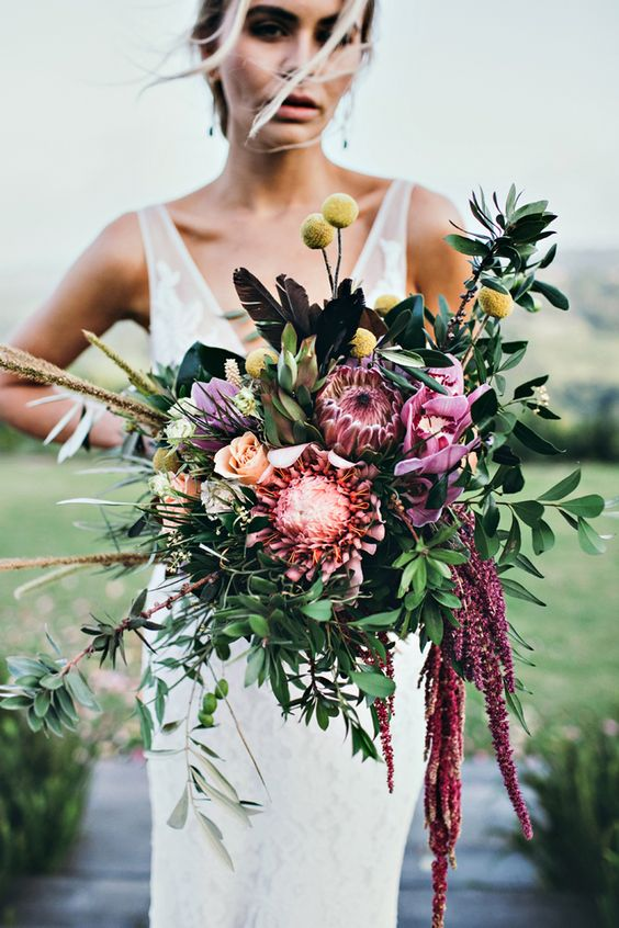 a colorful boho wedding bouquet in pink, fuchsia, with billy balls, greenery and some cascading elements