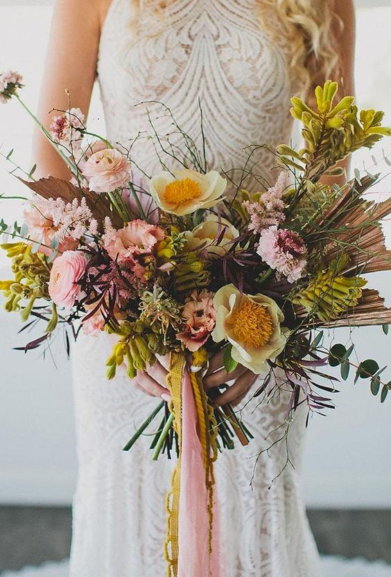 a colorful boho wedding bouquet in pink, mustard, with greenery and twigs plus some ribbons
