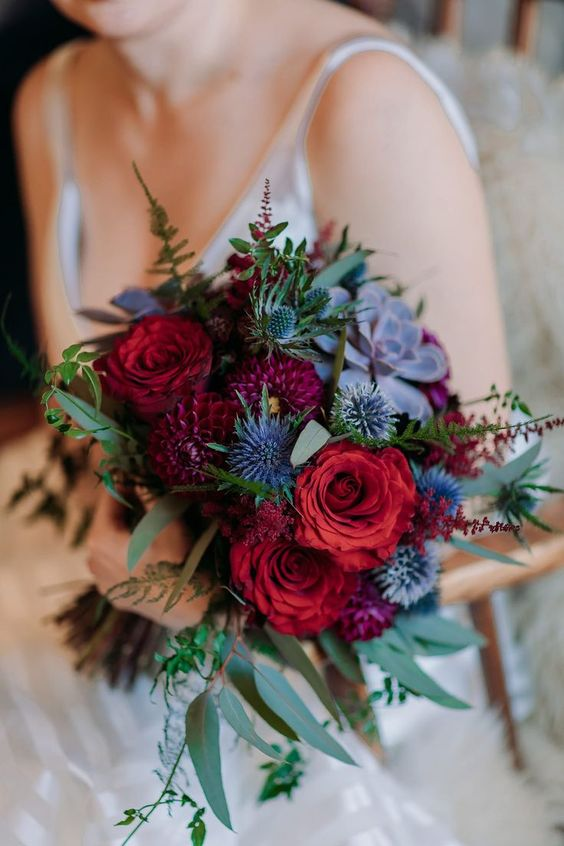 a colorful boho wedding bouquet in red, purple, with thistles and succulents looks super bold