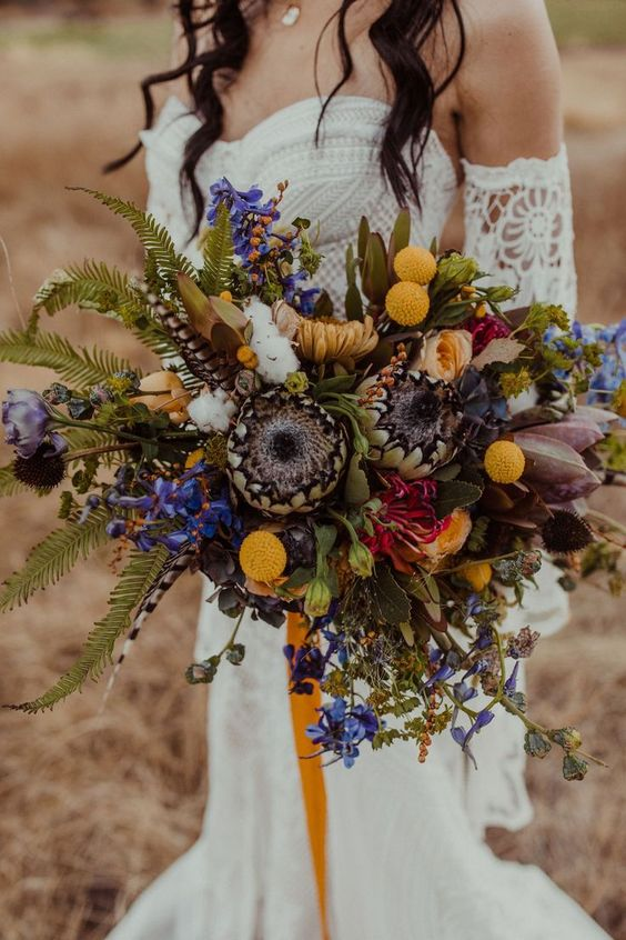a colorful boho wedding bouquet in yellow, purple, with feathers and greenery is great for a free-spirited bride