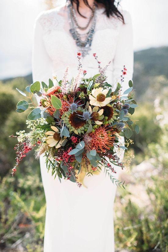 a colorful boho wedding bouquet of yellow blooms, pincushion proteas, thistles, greenery and some little red blooms