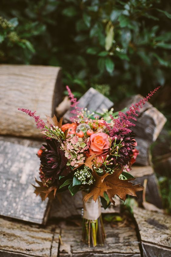 a colorful fall wedding bouquet with pink, deep purple blooms, greenery and fall leaves for a woodland wedding