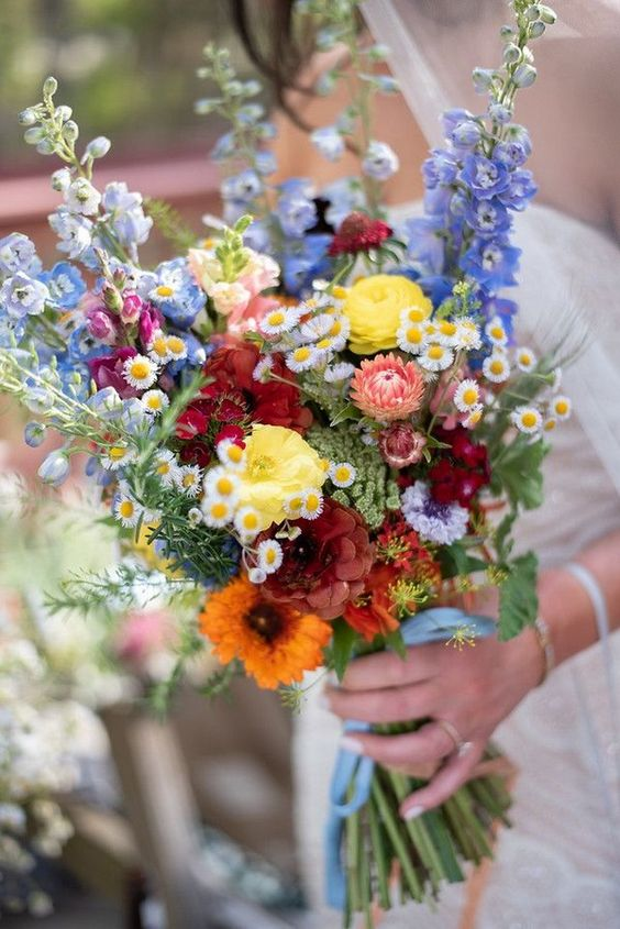 a colorful summer boho wedding bouquet in blue, yellow, pink, red and orange plus greenery