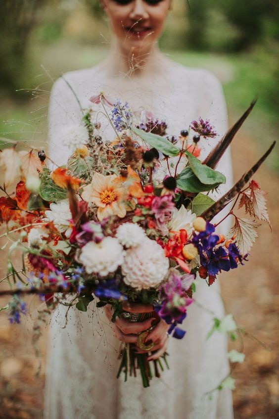 a colorful summer boho wedding bouquet in pink, orange, purple, blush, with lots of greenery and feathers