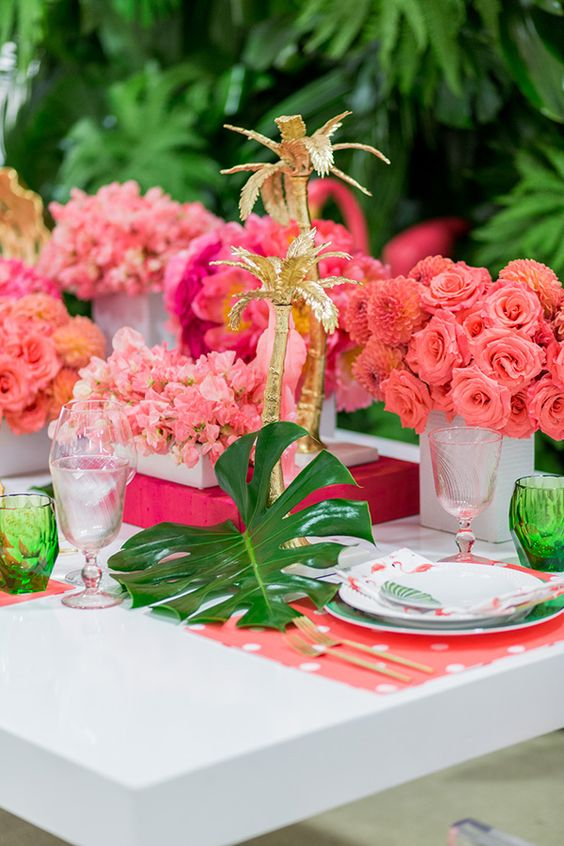 a colorful tropical wedding tablescape with pink blooms, gilded palm trees, pink placemats and colored glasses