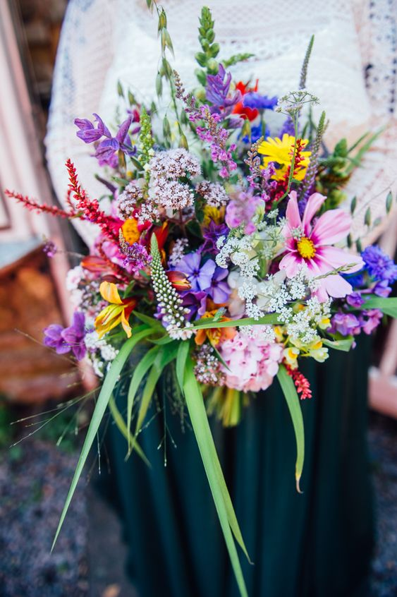 a colorful wedding bouquet with pink, purple, yellow and red blooms and greenery and grasses is wow and chic