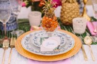 a colorful wedding tablescape with a pink napkin, gold chargers and cutlery, pineapples on the table and bold blooms
