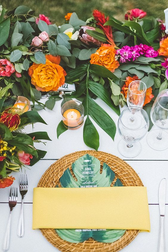 a colorful wedding tablescape with bold blooms and greenery, candles, woven chargers and tropical leaf menus
