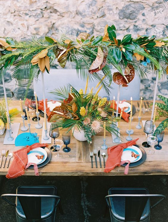 a colorful wedding tablescape with greenery, leaves and yellow blooms, blue stationery and red napkins
