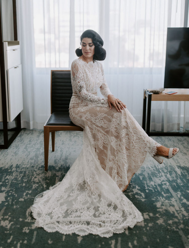 a creamy lace wedding dress with long sleeves, a high neckline, a trian and white block heels is ideal for an Old Hollywood wedding