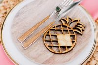 a creative and bright wedding table setting with a woven charger, neutral and wooden plates, pink napkins and a wood burnt pineapple