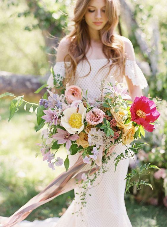 a creative textural boho wedding bouquet in bright pink, blush, marigold, purple and with lots of greenery