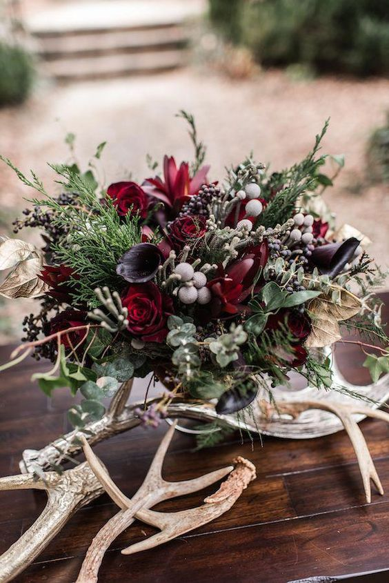 a dark and moody woodland wedding centerpiece with antlers, dark and deep red blooms and textural greenery and berries