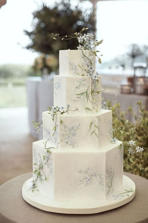 a delicate vintage-inspired wedding cake with blue flowers, greenery and some natural blooms on top