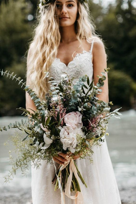 a dimensional boho and woodland wedding bouquet of various types of greenery, pink and blush blooms and ribbons