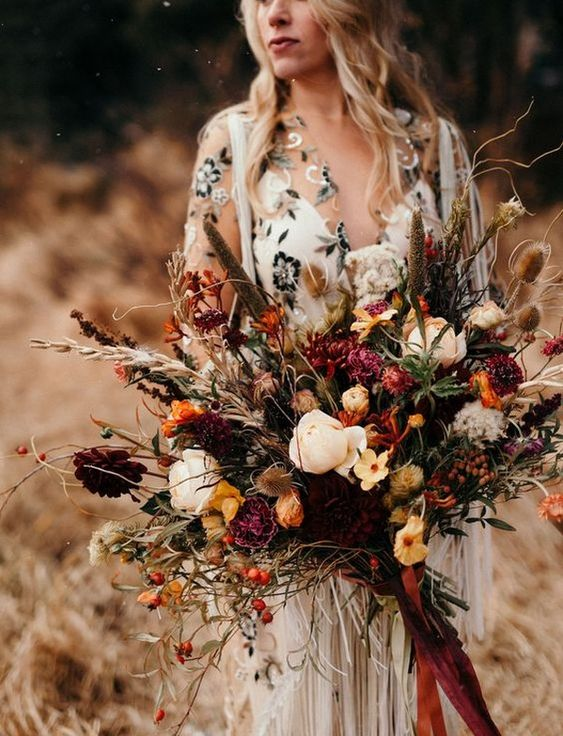 a fall wedding bouquet with marigold, burgundy and pink blooms, feathers, dried touches and berries