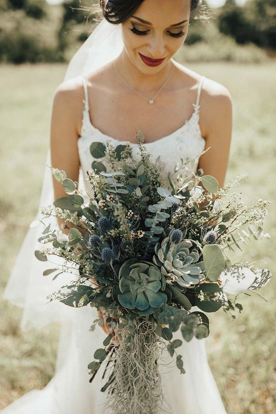 a fantastic greenery wedding bouquet with succulents, thistles and eucalyptus plus grasses for a woodland wedding