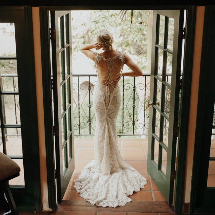 a fantastic lace mermaid wedding dress with a cutout back with chains and embellishments and a train is a gorgeous statement