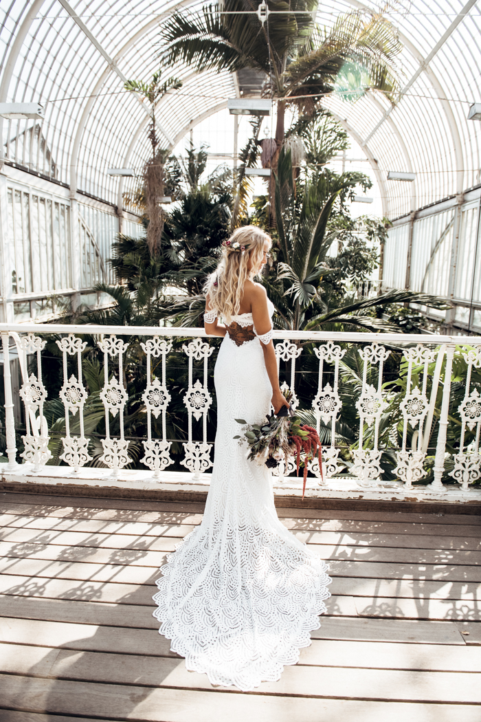 a fantastic off the shoulder lace mermaid wedding dress with a train that showed off a tattoo on the back