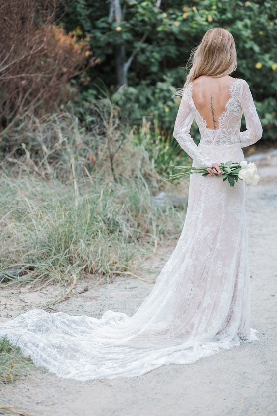 a fitting lace wedding dress with long sleeves, an open back and a train is very chic and refined