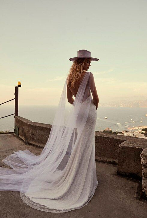 a fully embellished mermaid wedding dress with a low back, a small train and a tulel capelet plus a hat for a slight boho feel