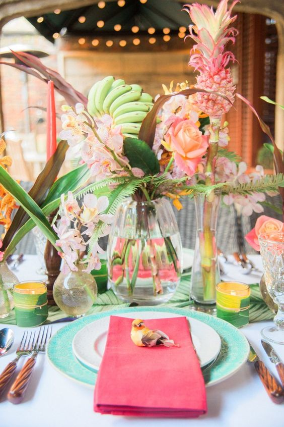 a fun colorful wedding tablescape with turquoise chargers, pink napkins, candles, pink blooms and leaves and fruits on stands