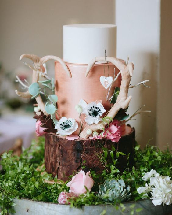 a fun woodland wedding cake with a wood tier, a copper and a white one, with sugar blooms and antlers