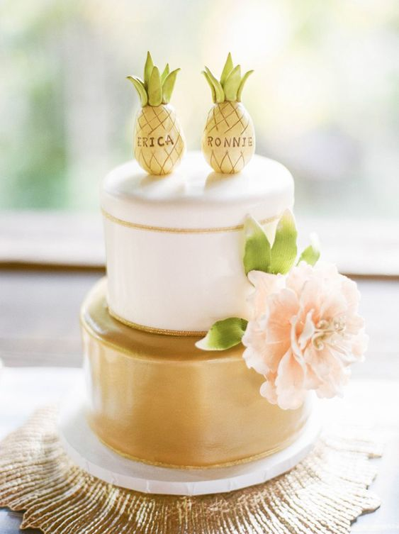 a glam gold and white wedding cake with a pink bloom and funny pineapple toppers is a lovely and cool idea
