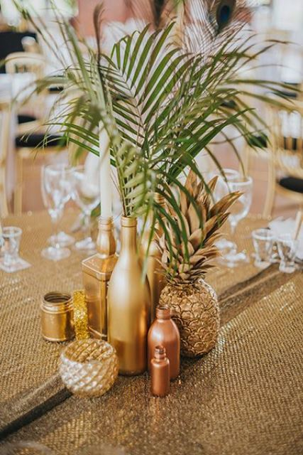 a glam metallic wedding centerpiece of a gilded pineapple, gold and copper vases and bottles with leaves and a gold candleholder