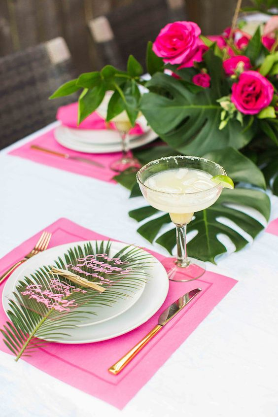 a glam tropical summer wedding tablescape with pink placemats, bright blooms and leaves and acrylic menus