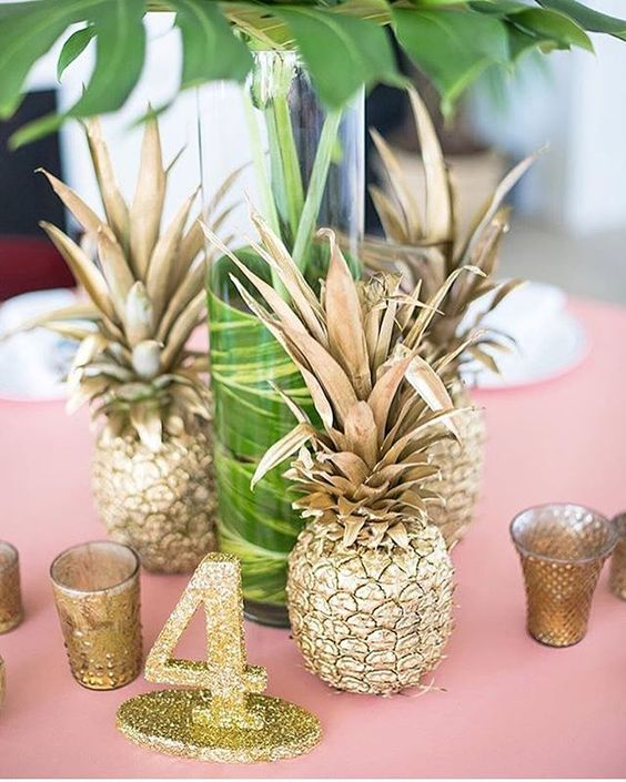 a glam wedding centerpiece of gilded pineapples a gold glitter table number, a tall vase with foliage and metallic candleholders