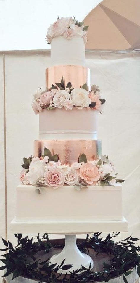 a gorgeous formal wedding cake with white and blush tiers, rose gold tiers, white and blush blooms and foliage