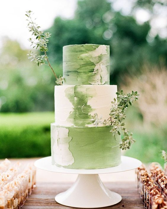 a gorgeous green and white wedding cake with brushstrokes and fresh greenery decor for a spring wedding
