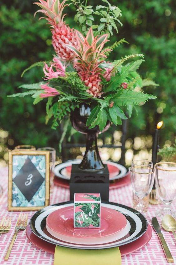 a gorgeous wedding centerpiece of a black vase, ferns, pink blooms and a pink pineapple is a lovely and bright idea