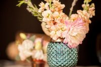 a green pineapple-shaped vase with pastel blooms and a wood slice under it for a lovely wedding centerpiece