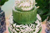 a green wedding cake with white leaf patterns and a mini pineapple on top for a bright tropical wedding