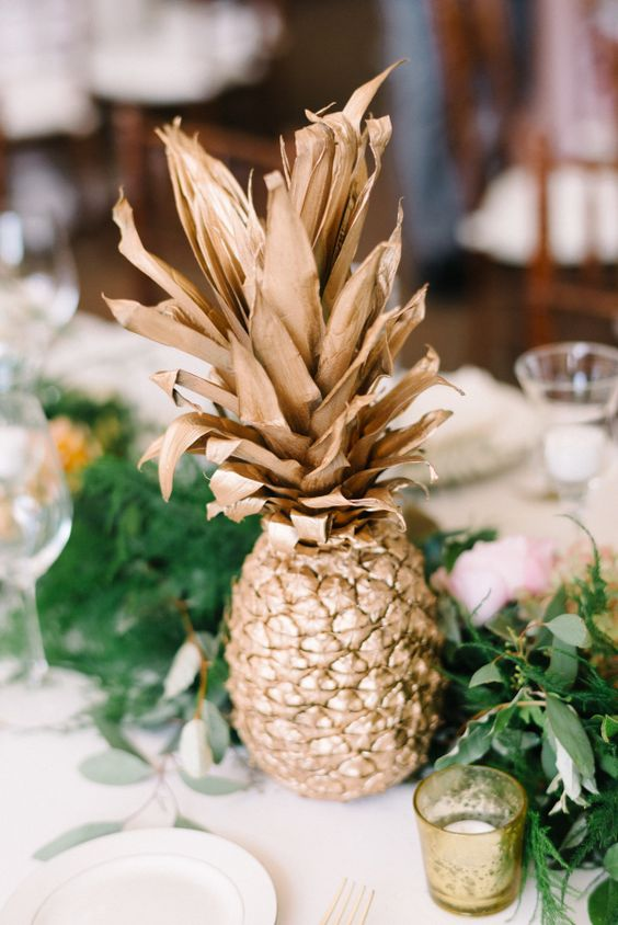 a greenery table runner dotted with pink and orange blooms and accented with a gilded pineapple for a modern tropical wedding
