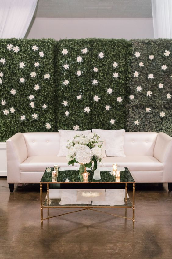 a greenery wall with white blooms that match the sofa create a cohesive lounge look