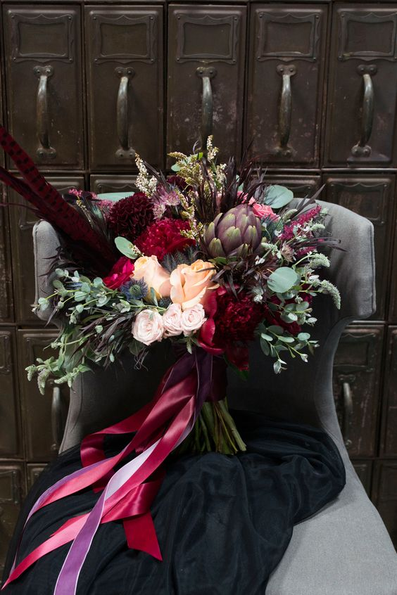 a jaw-dropping and bold fall wedding bouquet with blush, burgundy and deep purple blooms, greenery and thistles and colorful ribbons