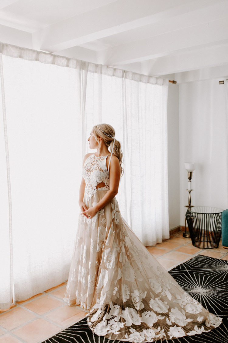 a jaw-dropping sleeveless wedding dress with a white lace bodice and a blush floral applique skirt with a long train