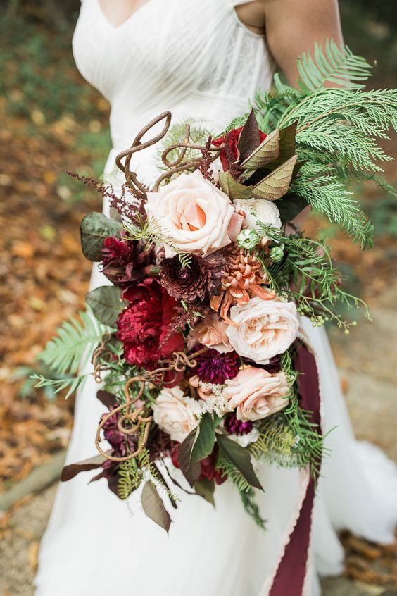 a jaw-dropping woodland wedding bouquet with blush and purple blooms, with foliage, fern and twigs is all cool