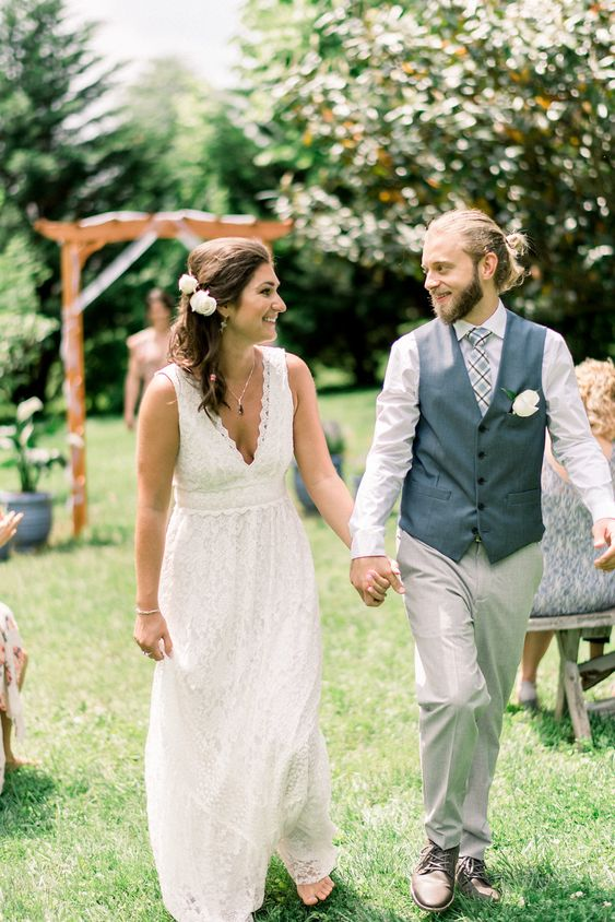 a lace A-line wedding dress with a V-neckline, no sleeves and an A-lien skirt for a boho backyard wedding